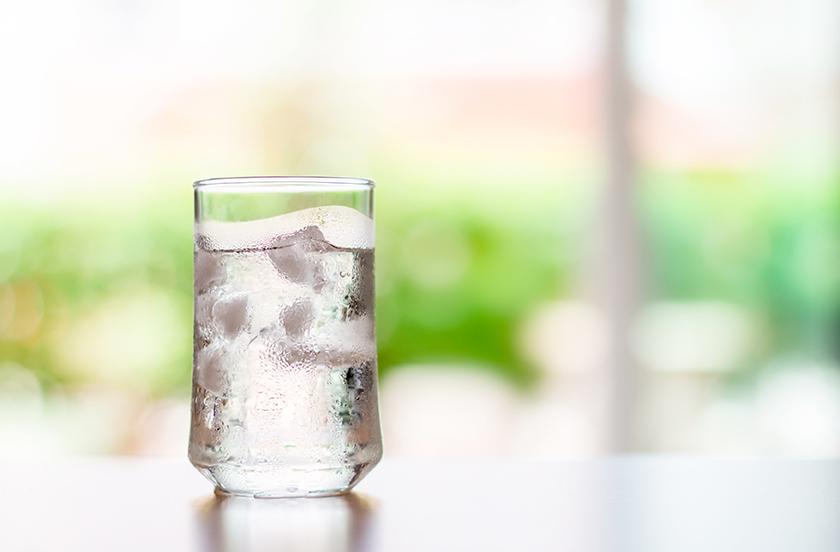 Das Bild zeigt ein Glas frisches Wasser mit Eiswürfel