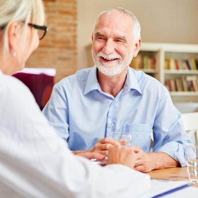 Erfreuter Pensionist im Gespräch mit Ärztin rund um Trinkwasser