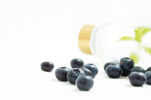 Glasflasche mit Wasser und arrangierte Heidelbeeren