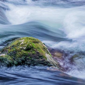 Wasser fließt über einen Stein