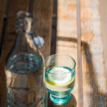 Glasflasche mit Wasser und Trinkglas mit einer Zitrone auf einem Holztisch
